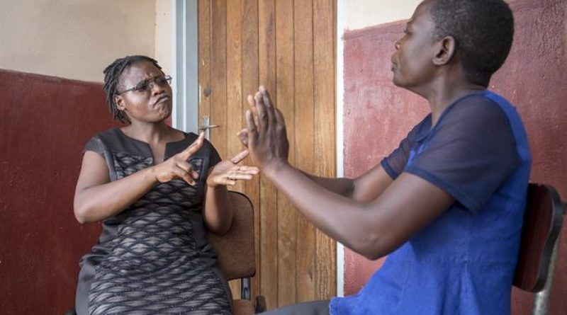 agness-left-communicating-in-sign-language-with-simbisu-right-who-is-supported-by-deaf-women-included-in-gweru-zimbabwe